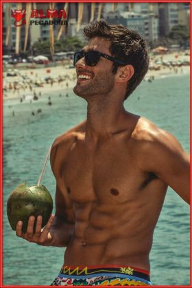Chico guapo en la playa con unos abdominales de escándalo