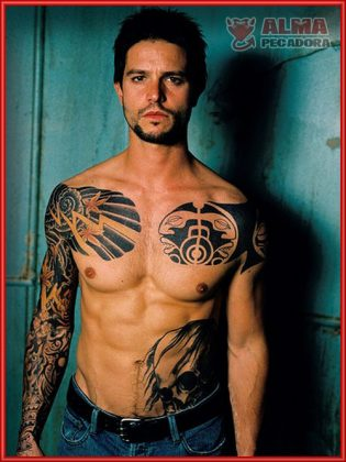 Chico musculoso con tatuajes luciendo abdominales